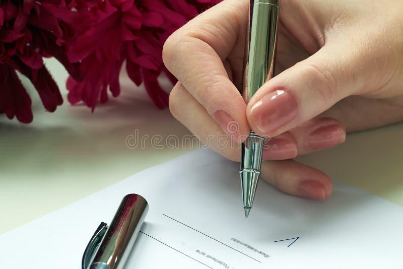 Mujer que se sienta en el escritorio de oficina que firma un contrato foto de archivo libre de regalías