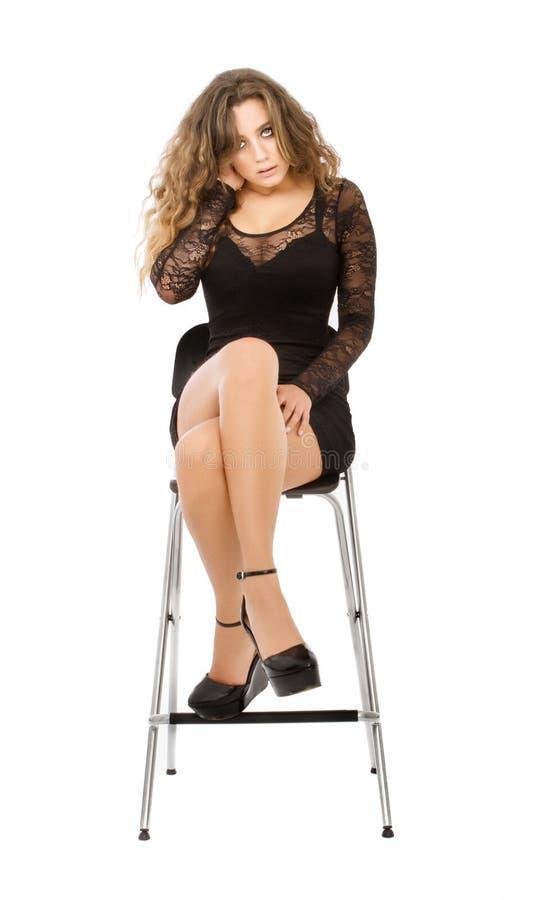 Mujer que se sienta en el fondo blanco y la cabeza conmovedora fotos de archivo libres de regalías