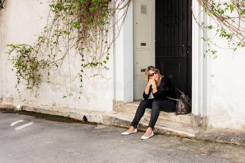 mujer que se sienta en el pórtico en la calle, pareciendo agujereada imagenes de archivo
