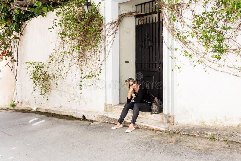 mujer que se sienta en el pórtico en la calle, pareciendo agujereada fotografía de archivo