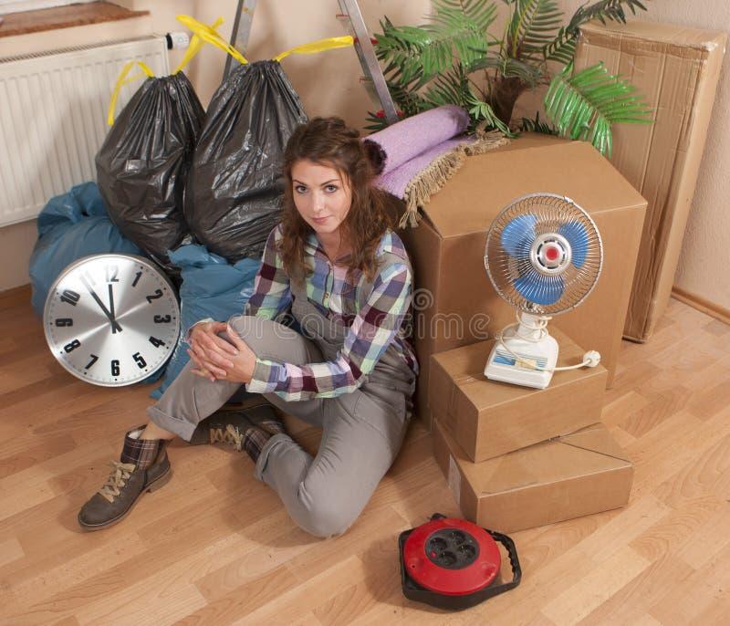 Mujer que se sienta en el piso entre la basura y las cajas móviles fotos de archivo libres de regalías