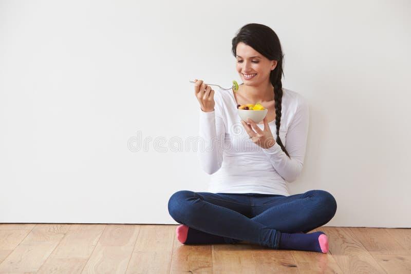 Mujer que se sienta en el piso que come el cuenco de fruta fresca imagenes de archivo