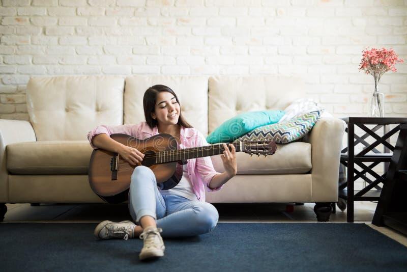 Mujer que se sienta en el piso que toca la guitarra imagen de archivo libre de regalías