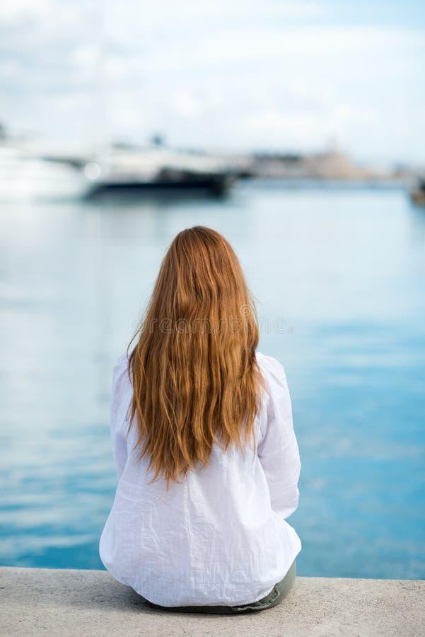 Mujer que se sienta en el puerto foto de archivo
