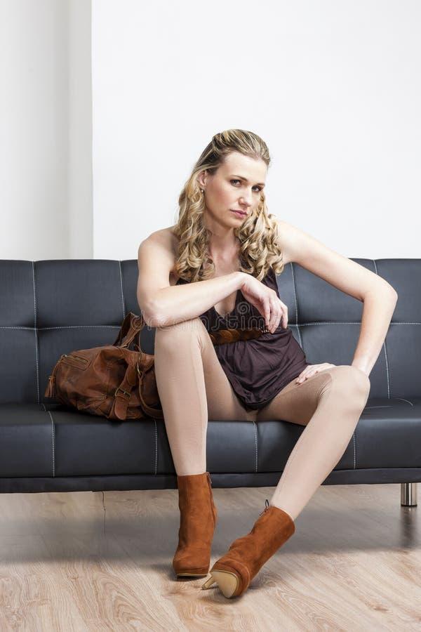 Mujer Que Se Sienta En El Sofá Foto de archivo