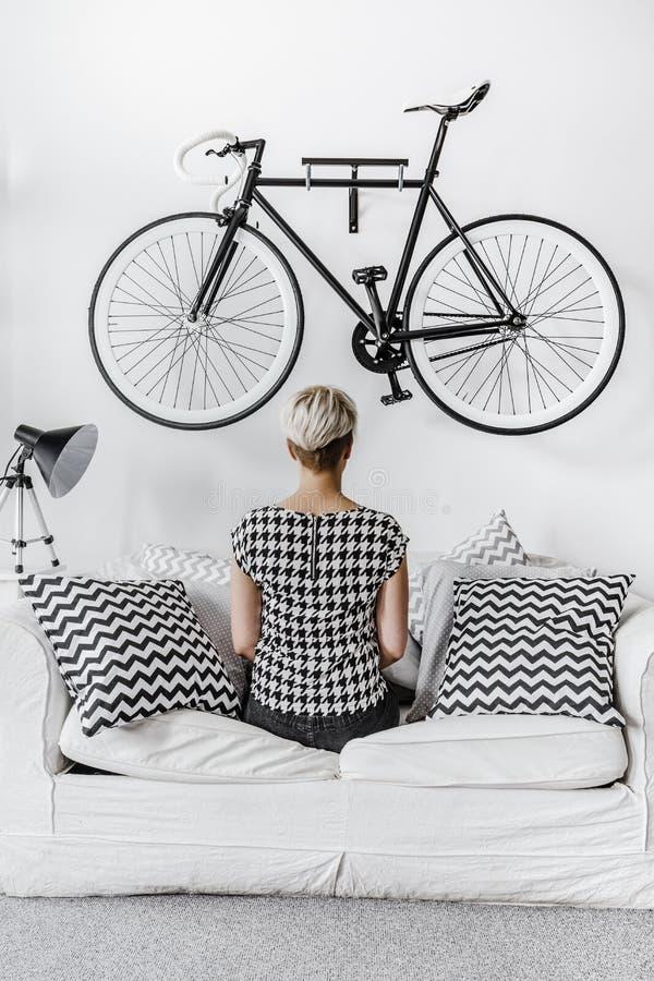 Mujer que se sienta en el sofá imagen de archivo libre de regalías