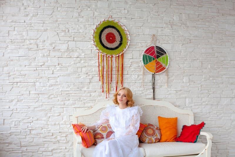 Mujer que se sienta en el sofá blanco imágenes de archivo libres de regalías