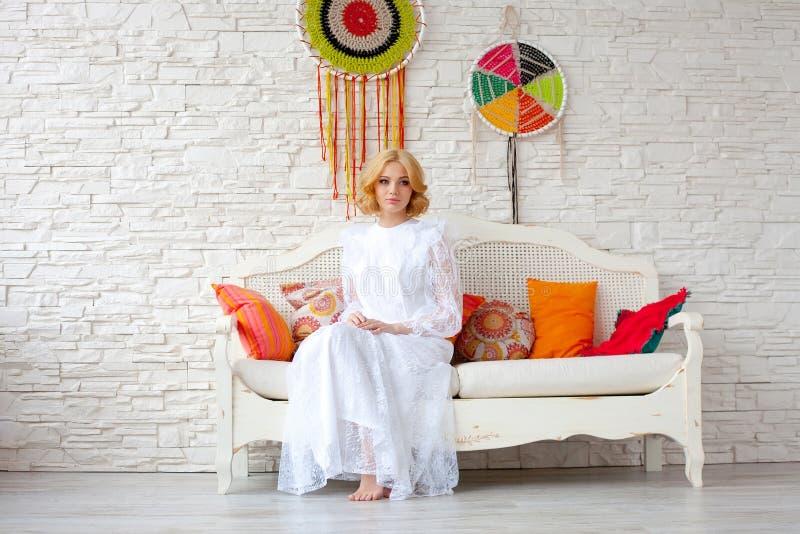 Mujer que se sienta en el sofá blanco fotos de archivo