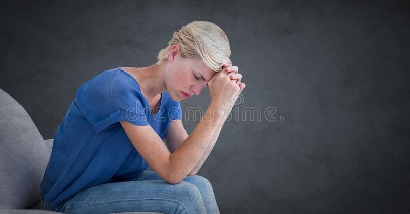 Mujer que se sienta en el sofá con la cabeza en las manos contra fondo gris con la capa del grunge imagen de archivo