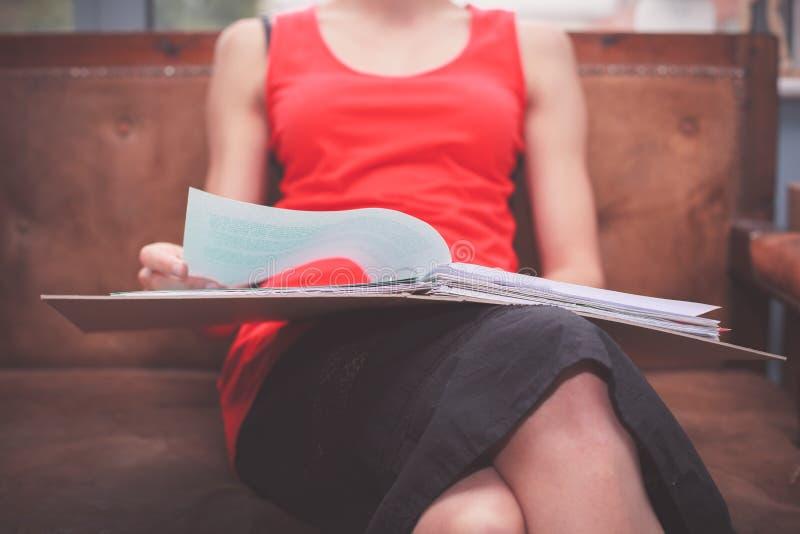 Mujer que se sienta en el sofá con los documentos imágenes de archivo libres de regalías