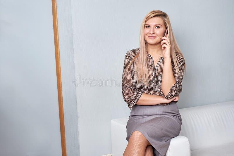 Mujer que se sienta en el sofá en la oficina y que habla en el teléfono fotos de archivo