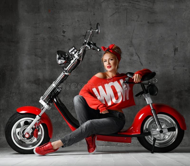 Mujer que se sienta en estilo modelo retro de la vespa de la bicicleta de la motocicleta en blusa roja y vaqueros fotografía de archivo