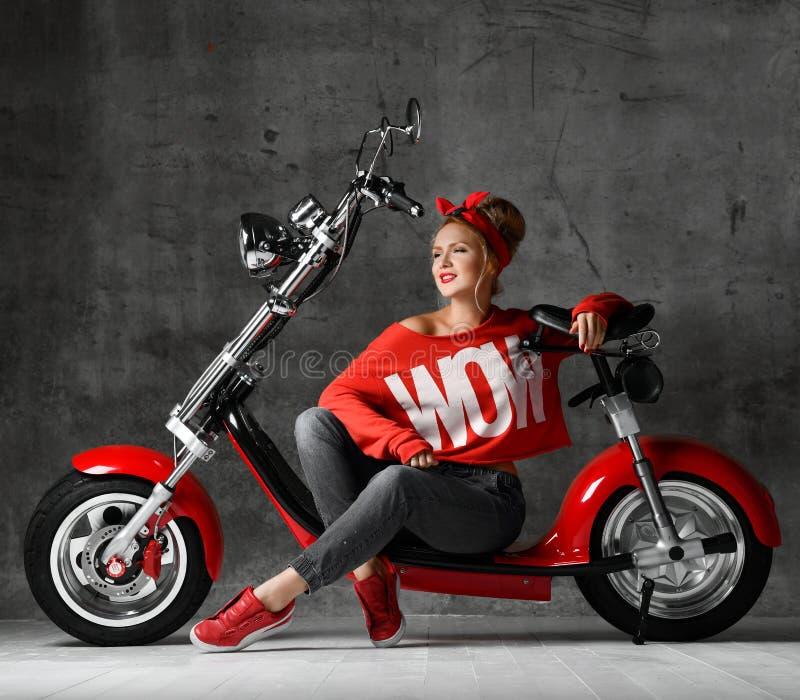 Mujer que se sienta en estilo modelo retro de la vespa de la bicicleta de la motocicleta en blusa roja y vaqueros imagen de archivo