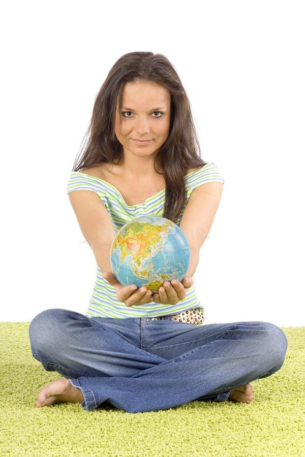 Mujer que se sienta en la alfombra verde - donante del globo imagen de archivo