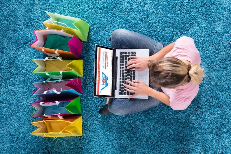 Mujer que se sienta en la alfombra y que hace compras en línea usando el ordenador portátil imagen de archivo