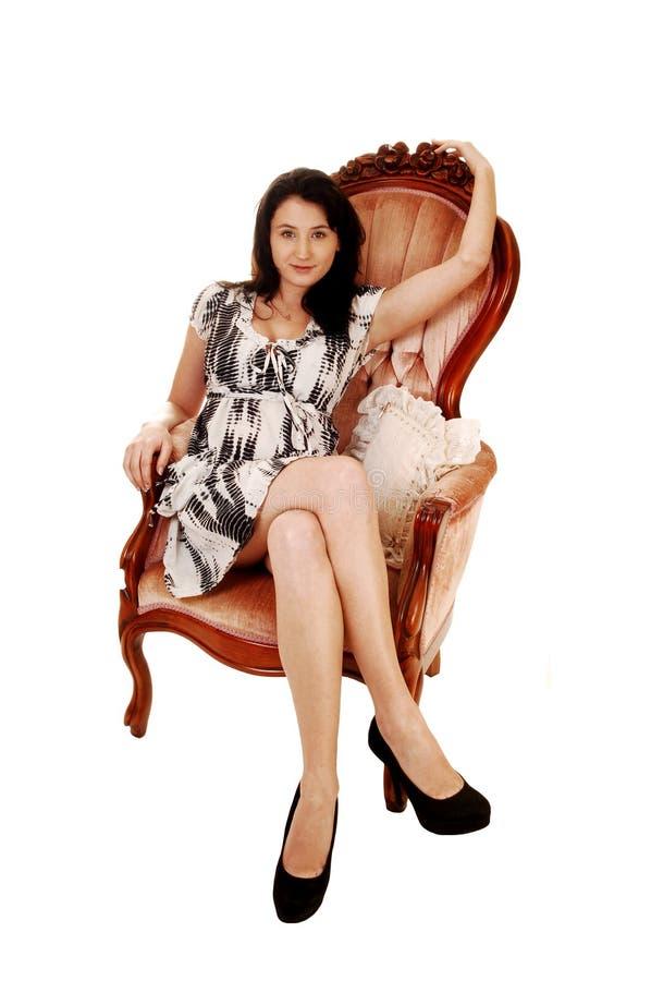 Mujer que se sienta en la butaca. fotografía de archivo libre de regalías