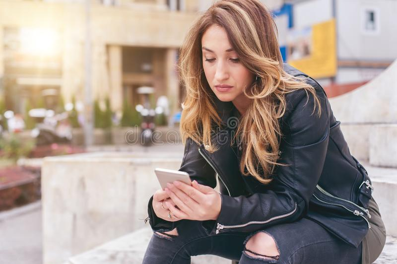 Mujer que se sienta en la calle de la ciudad, mensaje que mecanografía, charlando en smartp fotografía de archivo