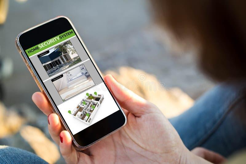 mujer que se sienta en la calle que sostiene su cctv del smartphone fotos de archivo