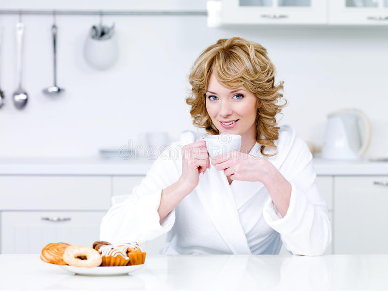 Mujer que se sienta en la cocina y el café de consumición imagen de archivo