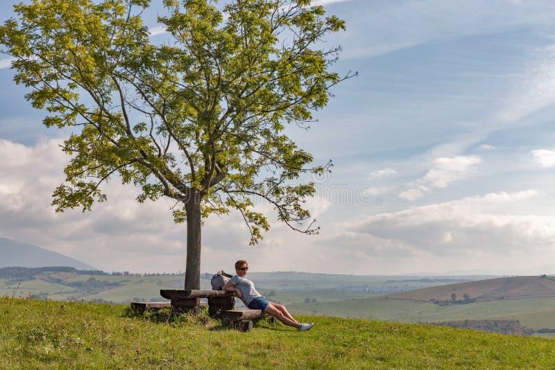 Mujer que se sienta en la colina del verano cerca de Liptovsky Trnovec, Eslovaquia imagen de archivo libre de regalías