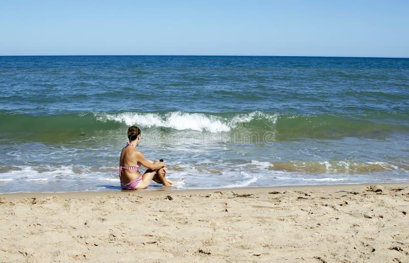 Mujer que se sienta en la costa fotografía de archivo