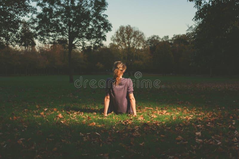 Mujer que se sienta en la hierba por la tarde foto de archivo