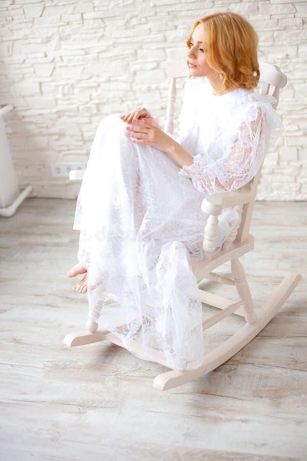 Mujer que se sienta en la mecedora blanca fotografía de archivo