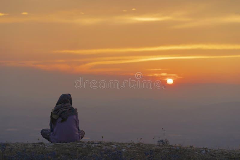 Mujer que se sienta en la montaña en la puesta del sol foto de archivo