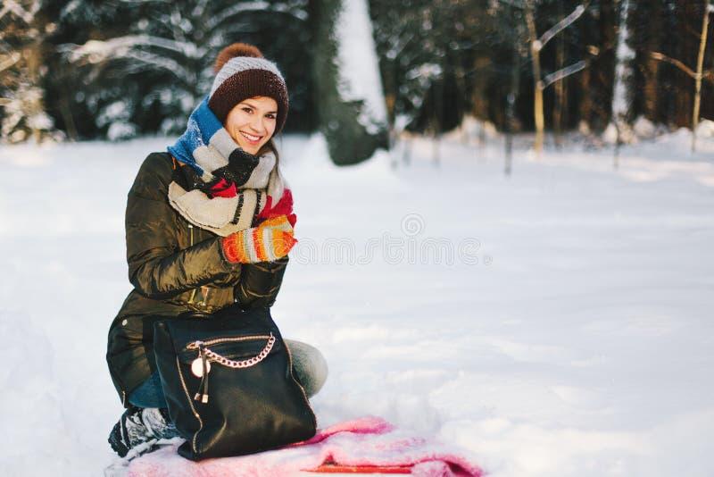Mujer que se sienta en la nieve en bosque foto de archivo