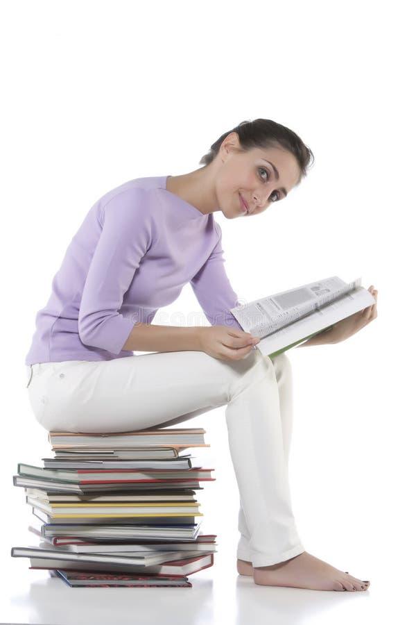 Mujer que se sienta en la pila de libros imagenes de archivo