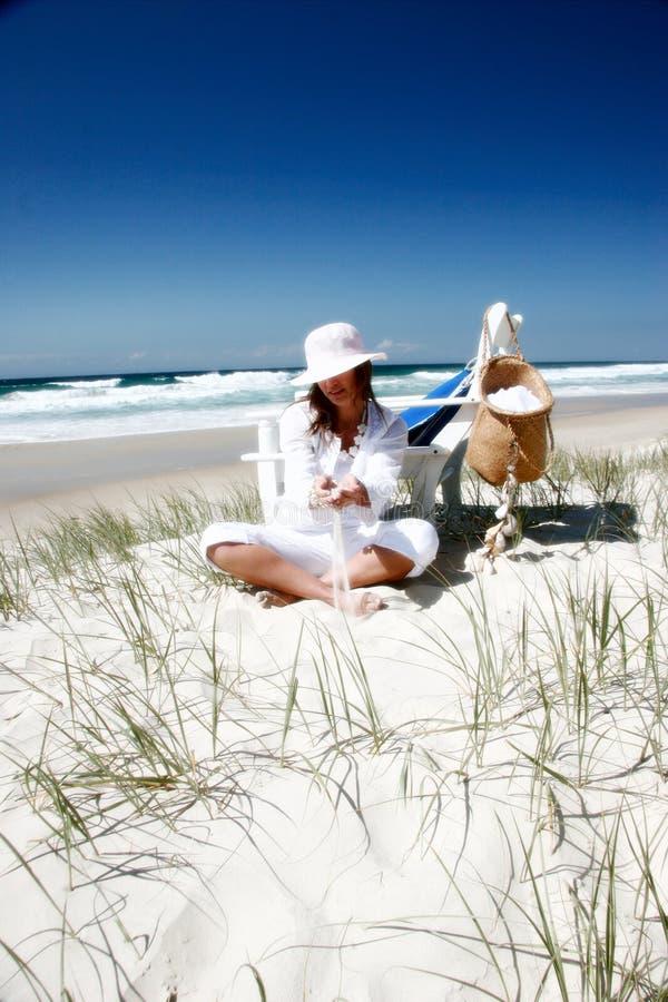 Mujer que se sienta en la playa imagen de archivo
