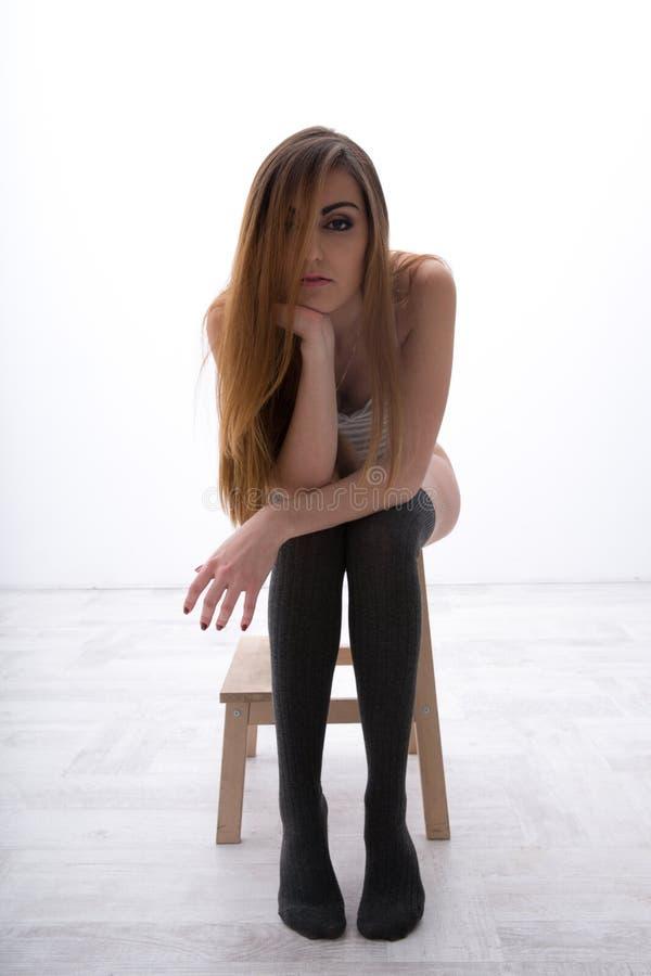 Mujer que se sienta en la silla de madera fotografía de archivo