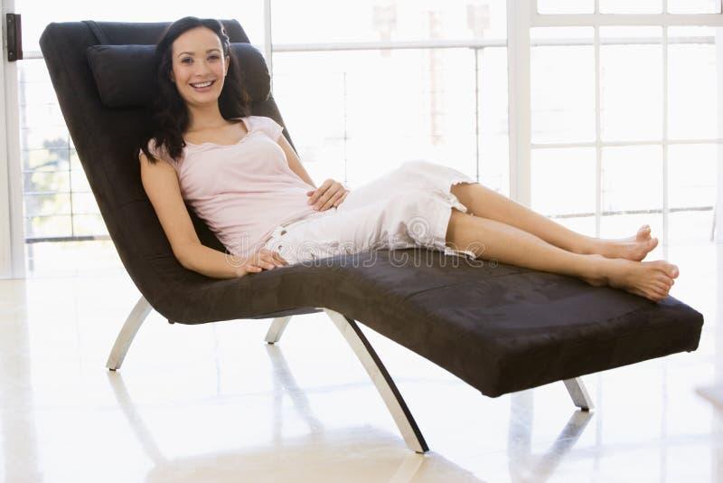 Mujer que se sienta en la sonrisa de la silla imagen de archivo libre de regalías