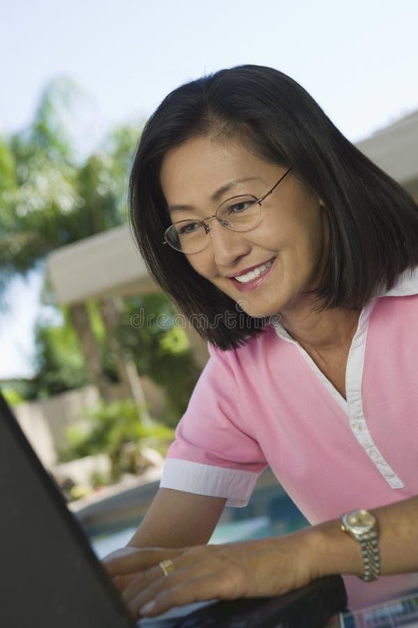 Mujer que se sienta en la tabla del patio trasero usando el ordenador portátil imagen de archivo libre de regalías