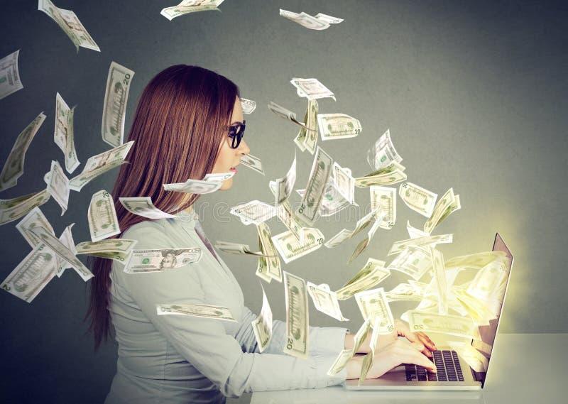 Mujer que se sienta en la tabla usando el trabajo en un ordenador portátil que hace el dinero foto de archivo libre de regalías