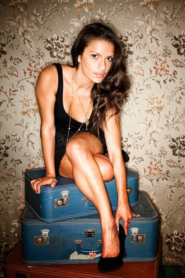 Mujer que se sienta en las maletas que ajustan su zapato foto de archivo libre de regalías