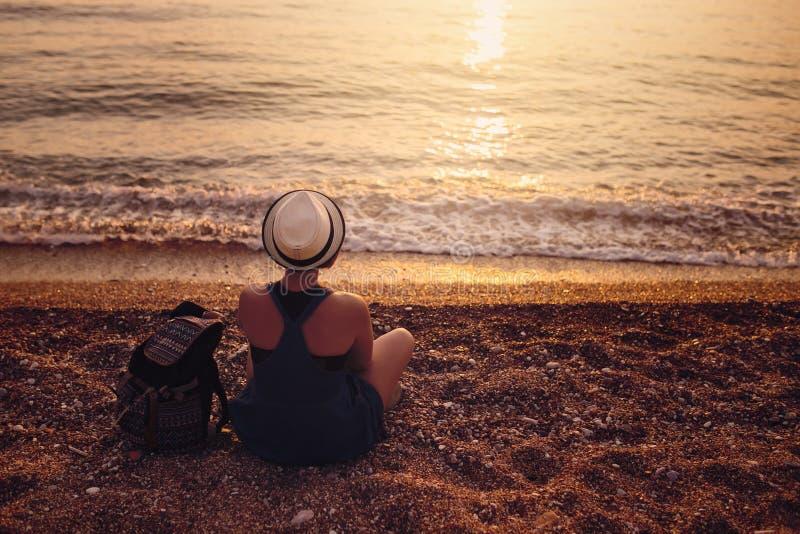 Mujer que se sienta en Pebble Beach cerca del mar fotos de archivo libres de regalías