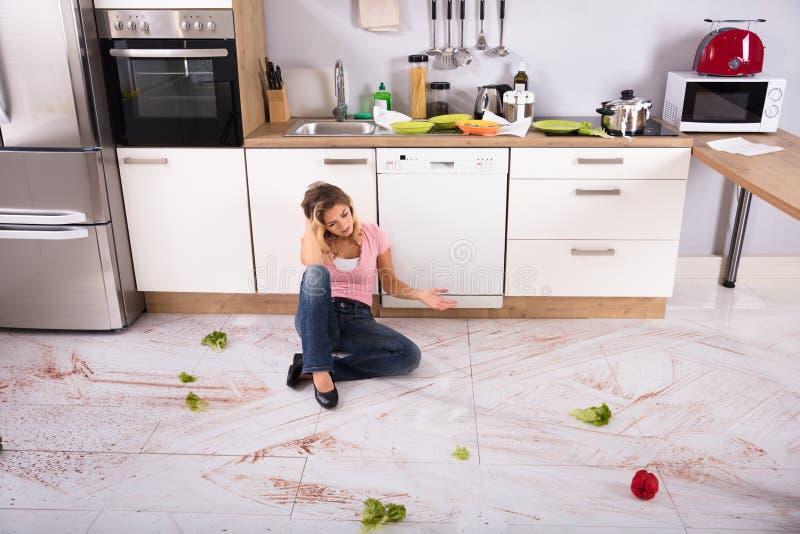 Mujer que se sienta en piso sucio de la cocina foto de archivo