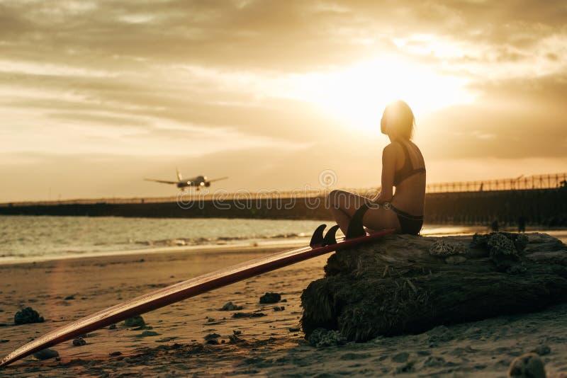 mujer que se sienta en roca con la tabla hawaiana en la playa en la puesta del sol con el aeroplano imagen de archivo