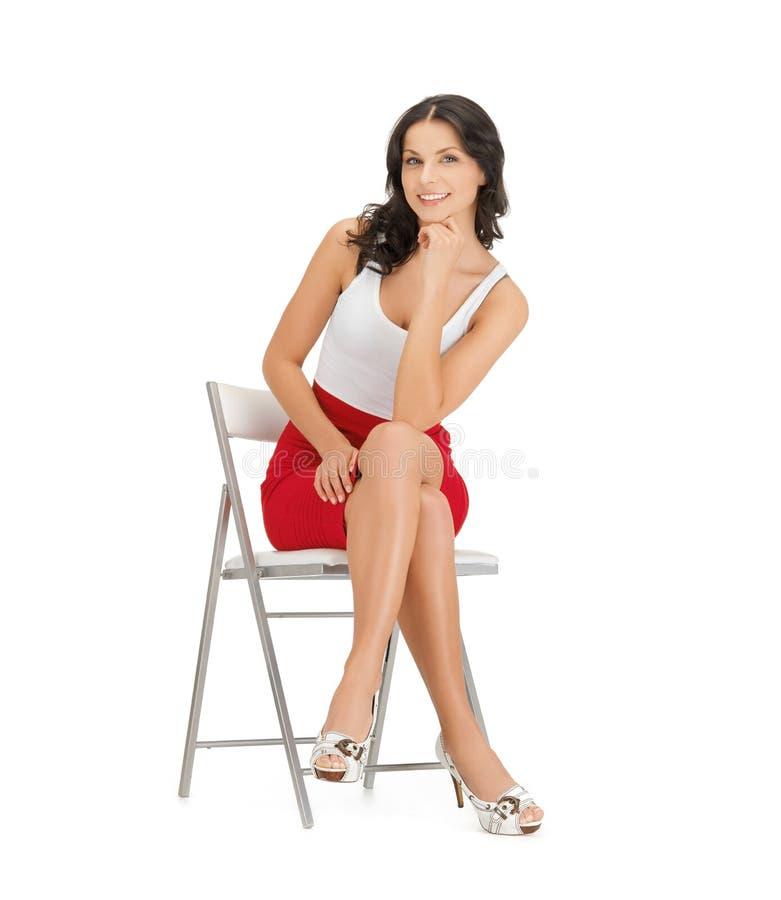 Mujer que se sienta en silla fotografía de archivo