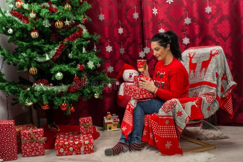 Mujer que se sienta en silla con los regalos de Navidad imagenes de archivo