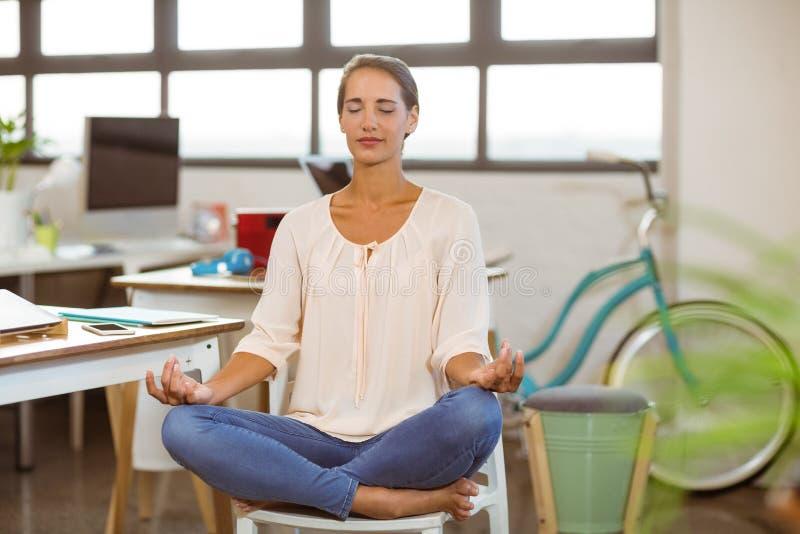 Mujer que se sienta en silla y que realiza yoga fotografía de archivo libre de regalías