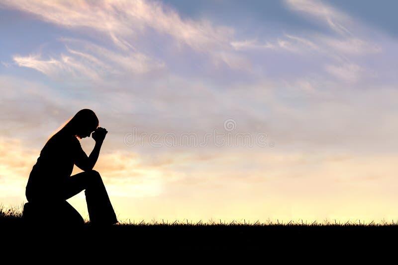 Mujer que se sienta en silueta del rezo imagen de archivo libre de regalías