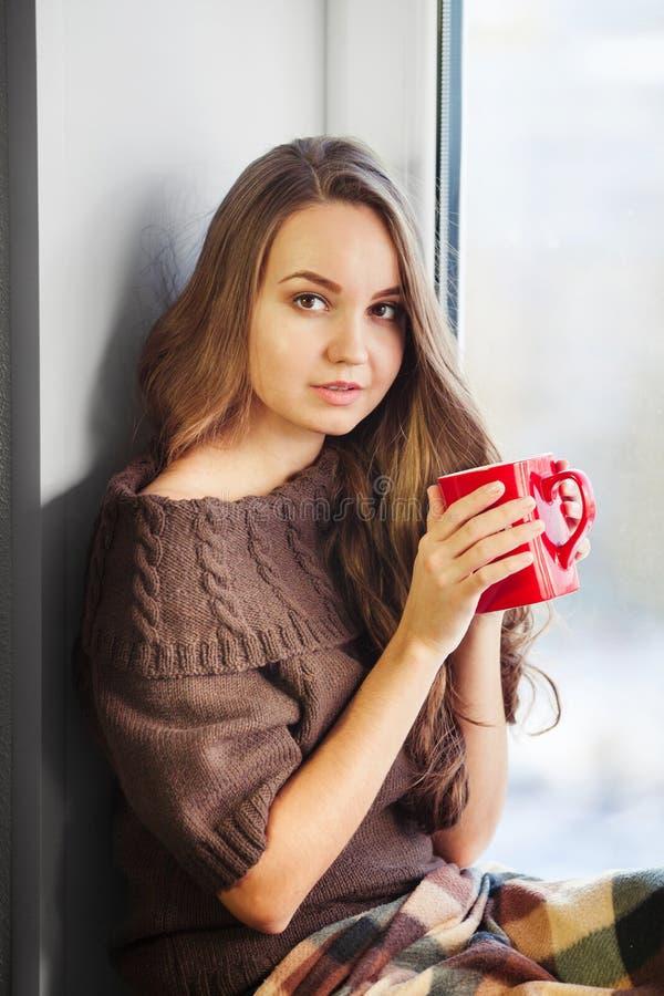 Mujer que se sienta en travesaño de la ventana y la taza de consumición de café fotos de archivo libres de regalías