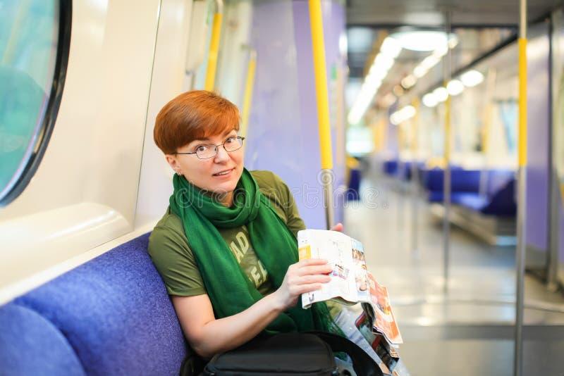 Mujer que se sienta en tren y que estudia el mapa de ruta Turista caucásico del pelirrojo en vidrios en el carro del metro viajer foto de archivo libre de regalías