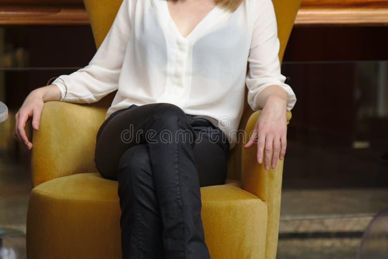 Mujer que se sienta en un asiento amarillo imagen de archivo