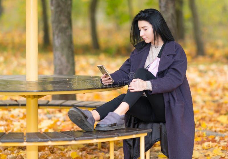 Mujer que se sienta en un asiento rústico en un parque del otoño imagen de archivo