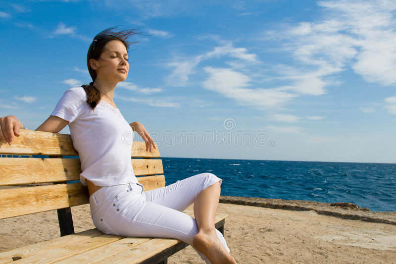 Mujer que se sienta en un banco fotos de archivo
