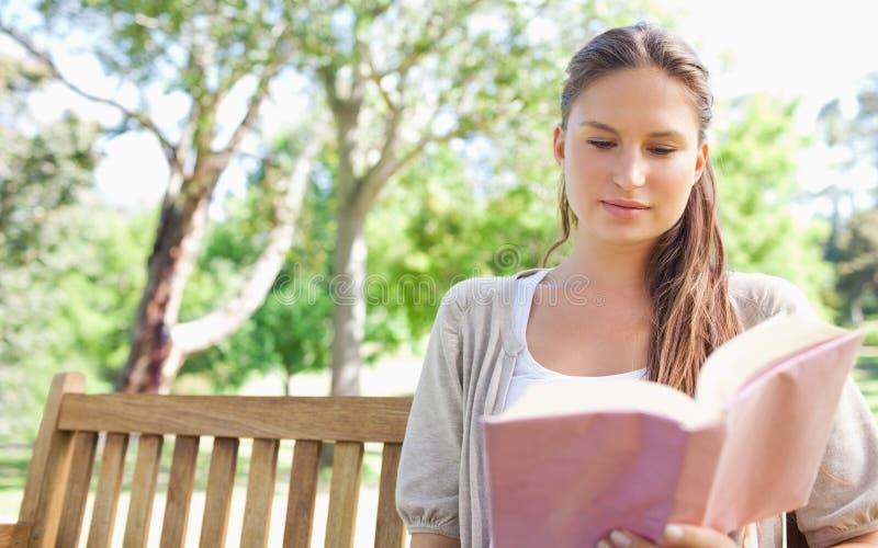Mujer que se sienta en un banco de parque mientras que lee un libro imágenes de archivo libres de regalías