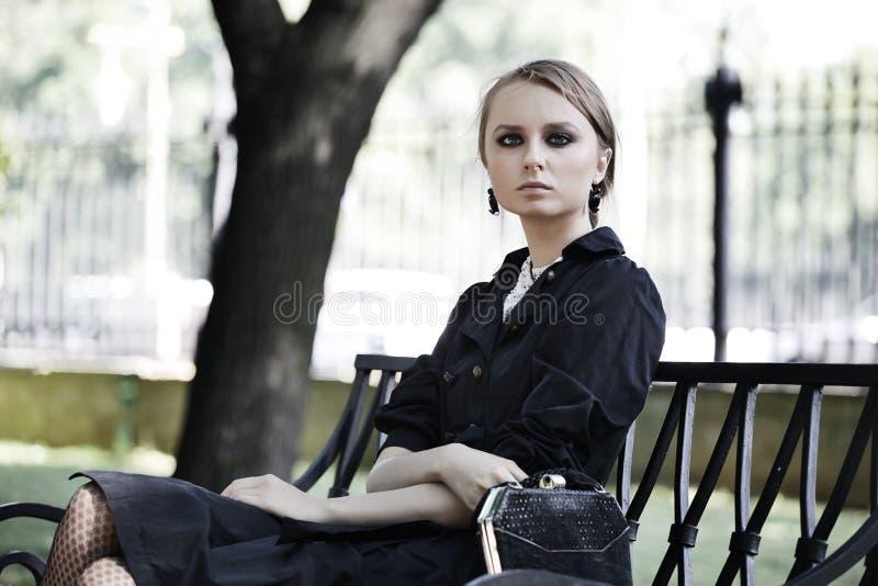 Mujer que se sienta en un banco en parque imagenes de archivo